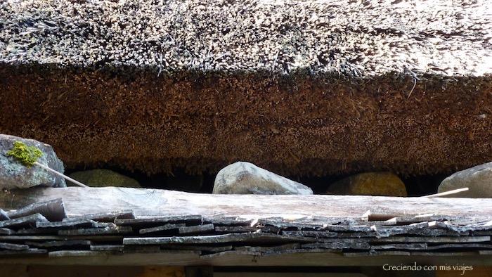 alternan capas de madera y piedra, y encima bloques de cañizo y paja